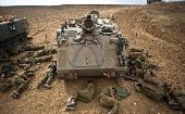 Israeli soldiers sleep on the ground next to an armoured personnel carrier outside the Gaza Strip July 15, 2014 (REUTERS)