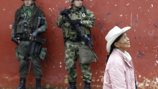 Soldiers stand guard as a woman walks past during a congressional election in Toribio in Cauca province in March (Reuters)
