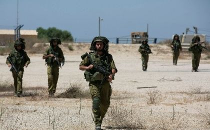 Israeli soldiers walk near the border with the central Gaza Strip July 14, 2014 (Reuters)