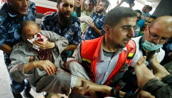 Palestinian policemen and medics carry a man, who medics said was wounded in Israeli shelling, at a hospital in Gaza City July 20, 2014.