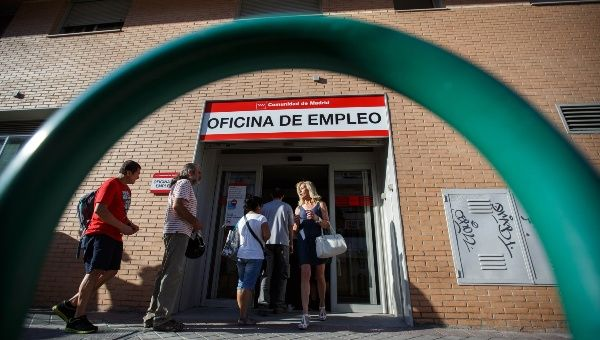 People enter and leave an employment office in Madrid, Spain.