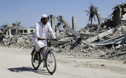A Palestinian man rides his bike past the ruins of destroyed houses in Khuzaa. (Photo: Reuters)
