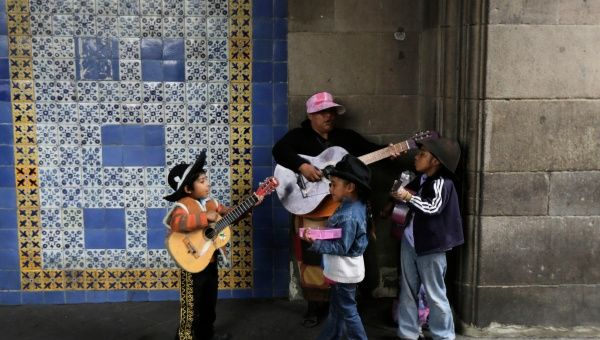A woman and her children play guitars as they wait for pedestrians to donate coins along a sidewalk near Zocalo Square in Mexico City August 7, 2014. (Photo: Reuters)