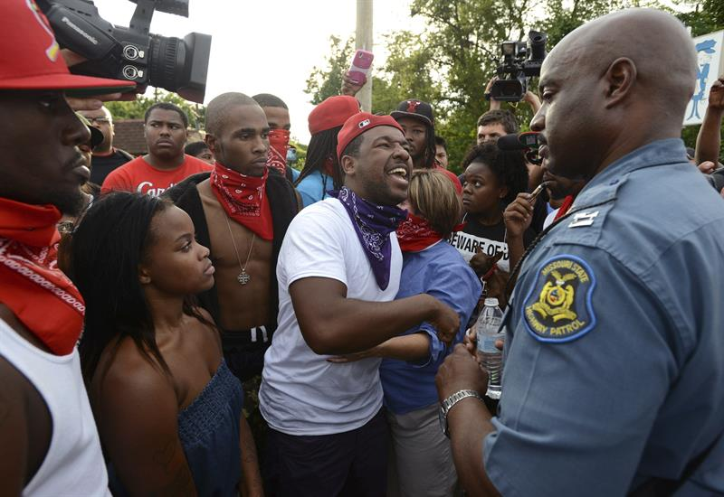 Captain Ron Johnson of Missouri's highway patrol, listens to the complaints of demonstrators over Michael Brown's killing in Ferguson, Missouri.