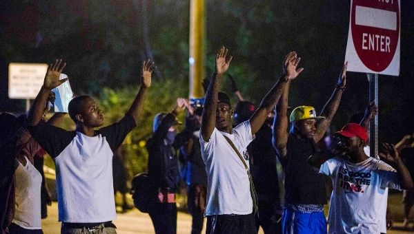 Demonstrators stand in the middle of West Florissant holding a street sign, with their hands up, towards the police. (Photo:Reuters)