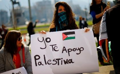 "A woman holds up a placard that reads ""I support you Palestine"" as supporters and members of the Palestine community in Chile gather during a rally for peace in Gaza, in Santiago, August 9, 2014 (Photo: Reuters)"