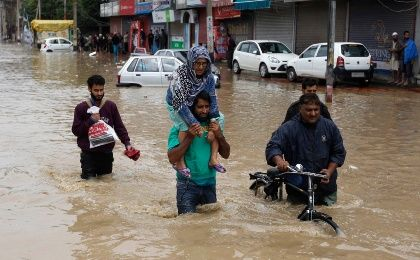 A Kashmiri man evacuates an elderly woman to a higher ground at a flooded road in Srinagar September 7, 2014 (Photo: Reuters)