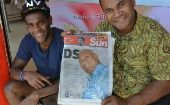 Fijian First Party supporters hold the local newspaper showing a front page photo of coup leader Voreqe Bainimarama, a day after elections, in Nadi, on September 18, 2014 (Photo: AFP)