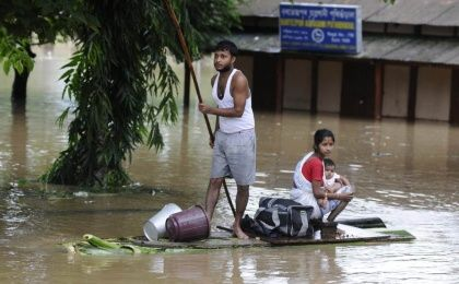 A villager uses a makeshirt raft to transport relatives through floodwaters in Bartezpur village, Guwahati on September 23, 2014. (Photo: AFP)