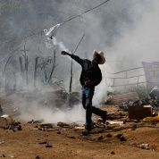 An opponent of the Tambor mining project throws back a tear gas canister that the riot police had fired while evicting protesters against the mining project in the community of La Puya in San José del Golfo on May 23, 2014. (Photo: Reuters)