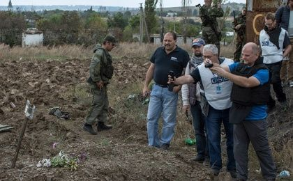 OSCE observers take pictures at the site where pro-Russian say is a mass grave with five bodies, in the town of Nizhnaya Krinka, eastern Ukraine, September 23, 2014. (Photo: Reuters/Marko Djurica)