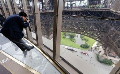 A visitor takes pictures as he stands on the new glass floor at the Eiffel Tower in Paris October 6, 2014 (Photo: Reuters)