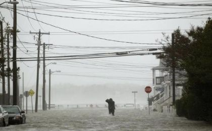 Powerlines hang overhead as a man wades through a street flooded during Hurricane Sandy in Ocean City, Maryland October 29, 2012. (Photo: Reuters)