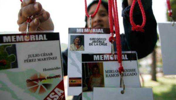 A woman hangs accreditations of journalists killed in recent years while covering the news in Mexico. (Photo: CPJ)