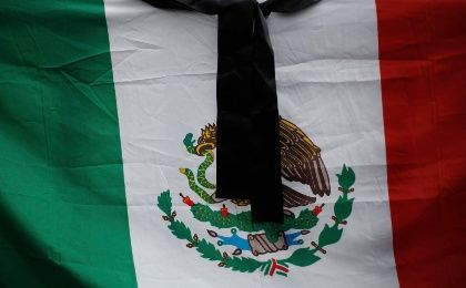 A black ribbon is seen over a Mexican flag during a protest for the fatal victims of the September 26 shooting against students from the Ayotzinapa Teacher Training College and members of a football team,  outside Palacio Nacional in downtown Mexico City November 1, 2014. (Photo: Reuters/Tomas Bravo)