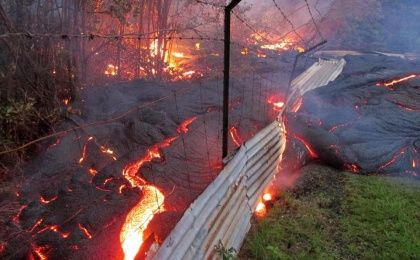 Lava from the Kilauea volcano in Pahoa, Hawaii overcomes a fence marking a private property on October 31, 2014. (Photo: AFP)