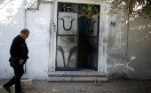 A man walks past a damaged door of a Fatah official's home after an explosion in Gaza City