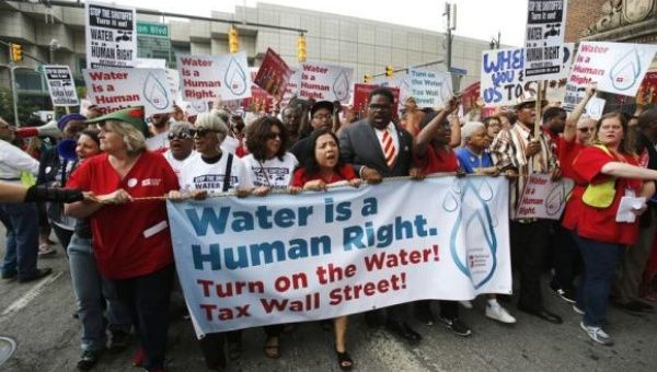 People hold a banner against the mass water shut-offs to Detroit citizens behind in their payments, during a protest in downtown Detroit, Michigan July 18, 2014. (Photo: Reuters)