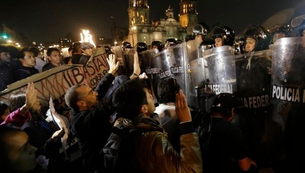 Demonstrators plead with riot police not to use violence during a protest in support of 43 missing Ayotzinapa students in Mexico City November 20, 2014. (Photo: Reuters)