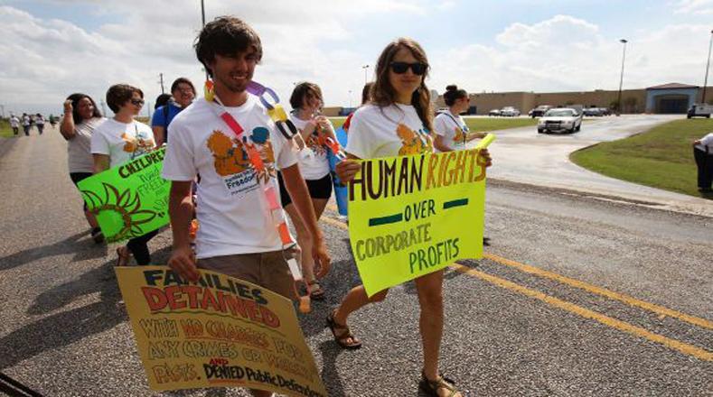 """""""Derechos humanos sobre las ganancias corporativas"""", reza el mensaje de la joven al frente."""