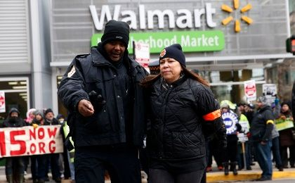 JoEllen Schlademan, of Oak Park, Illinois, is removed from the street by a police officer during a demonstration for higher wages and better working conditions, outside of a Walmart during Black Friday shopping in Chicago November 28, 2014. (Photo: Reuters/Andrew Nelles)