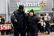 Jo Ellen Schlademan, of Oak Park, Illinois, is removed from the street by a police officer during a demonstration for higher wages and better working conditions outside a Wal-Mart during Black Friday shopping in Chicago Nov. 28, 2014.