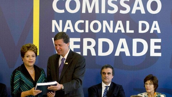 "Brazilian President Dilma Rousseff (L) receives the report from Pedro Dallari (2nd L), a member of the ""truth commission"", in Brasilia December 10, 2014."