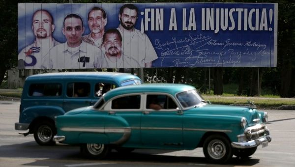Cars drive past a banner featuring five Cuban prisoners held in U.S. custody, two of whom were previously released, in Havana Dec. 17, 2014.
