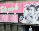 A man walks by a billboard in Havana with images of heroes of the Cuban Revolution