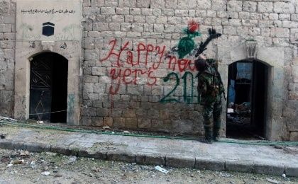 A Free Syrian Army fighter sprays graffiti on a wall prior to the new year in Aleppo Dec. 31, 2014
