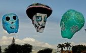 "A balloon depicting ""La Calavera Catrina,"" the elegant skull, is flanked by decorated skulls. The imagery is common at Mexico"