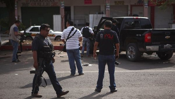 Plainclothes police stand next to a bullet-riddled pickup truck after a shooting between federal forces and armed civilians in the town of Apatzingan, Michoacan Jan. 6, 2015.