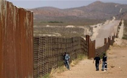Mexican men walk along the border wall that separates Agua Prieta, Sonora, Mexico from Douglas, Arizona, U.S., May 23, 2006. Republicans plan on cracking down on immigration by increasing security on the border.