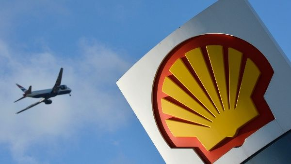 A passenger plane flies over a Shell logo at a petrol station in west London, January 29, 2015