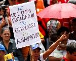 A pro-Venezuelan government protester holds up a banner that reads,