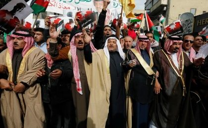 Jordanian protesters hold up pictures of Jordan's King Abdullah and Jordanian pilot Muath al-Kasaesbeh, as they chant slogans during a march after Friday prayers in downtown Amman February 6, 2015.