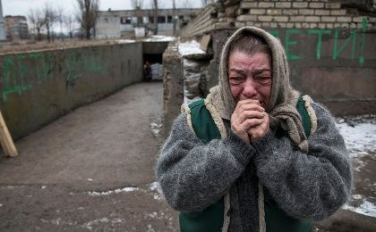 An elderly woman in Eastern Ukraine reacts as friends board a bus to flee due to a military conflict February 4, 2015.