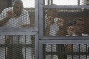 Al Jazeera journalists (L-R) Mohamed Fahmy, Peter Greste and Baher Mohamed stand behind bars at a court in Cairo.