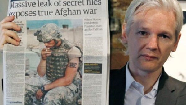 WikiLeaks founder Julian Assange holds up a copy of the Guardian after thousands of US military documents were leaked and exposed.