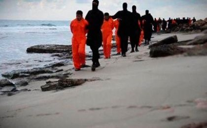 Men in orange jumpsuits purported to be Egyptian Christians held captive by the Islamic State group are marched by armed men along a beach said to be near Tripoli, in this still image from an undated video made available on social media on Feb. 15, 2015.