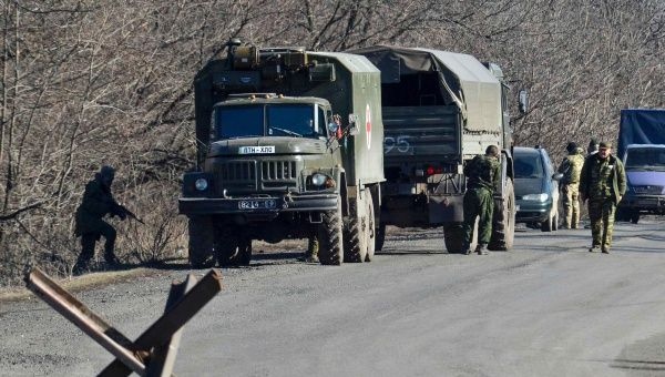 Trucks from the Ukrainian armed forces and separatists deliver the bodies of the fallen in recent fighting for exchange on a road in eastern Ukraine.