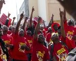 Members of the National Union of Metal Workers of South Africa (NUMSA) point at workers at a construction site not taking part in the strike during a protest on the streets of Durban