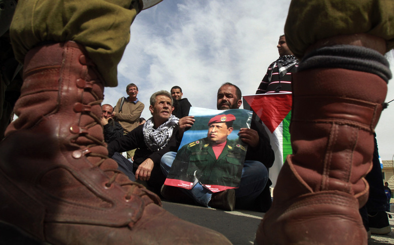 Palestinian protesters hold a banner of President Chavez during a protest in the West Bank, 2013.