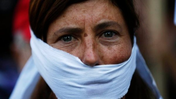 A woman protests against the new law for policing demonstrations, in central Madrid.