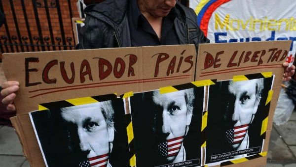 A supporter of Julian Assange holds a placard with the slogan
