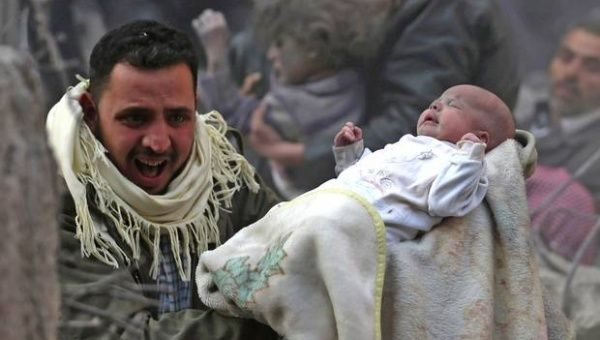 A man tries runs carrying a baby as war-torn Syria enters its fifth year of conflict.