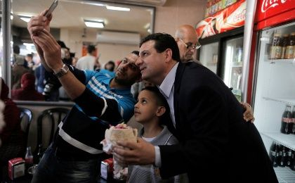 Ayman Odeh (R), head of the Joint Arab List, poses for a photograph together with people at a restaurant during a campaign stop in the northern Israeli city of Acre March 13, 2015.