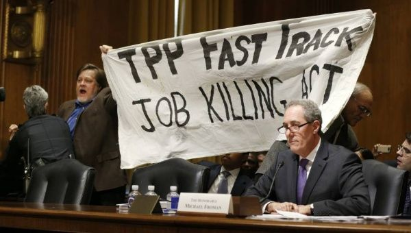 A policewoman removes a man protesting the Trans-Pacific Partnership as U.S. Trade Representative Michael Froman (right) testifies at a Senate Finance Committee hearing in Washington on Tuesday.