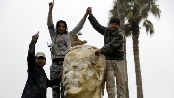Syrian rebels in Idlib destroy a statue of Hafez Assad, father of President Bashar Assad.