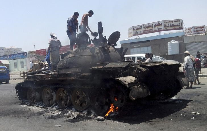 People stand on a tank that was burnt during clashes on a street in Yemen's southern port city of Aden March 29, 2015.